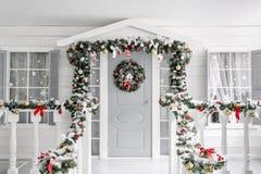De ochtend van Kerstmis portiek een plattelandshuisje met een verfraaide deur met een Kerstmiskroon Het sprookje van de winter stock afbeeldingen