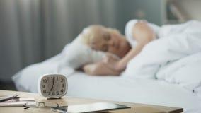 In de ochtend Vrouwelijke slaap op middelbare leeftijd in bed Mening van lijst met klok stock footage