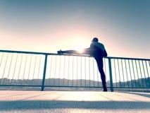 De ochtendagent in lange zwarte beenkappen maakt zich lichaam het uitrekken op brugweg Het openlucht uitoefenen royalty-vrije stock afbeeldingen