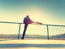 De ochtendagent in lange zwarte beenkappen maakt zich lichaam het uitrekken op brugweg Het openlucht uitoefenen royalty-vrije stock foto