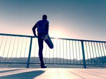 De ochtendagent in lange zwarte beenkappen maakt zich lichaam het uitrekken op brugweg Het openlucht uitoefenen stock afbeeldingen