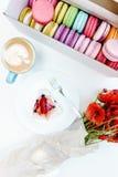 De ochtendpapaver bloeit boeket en Franse macarons met smakelijke cake en cappuccino op witte lijst Stock Foto