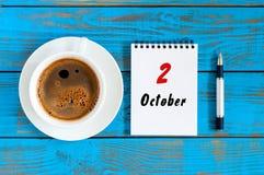2 de octubre Día 2 del mes de octubre, calendario con la taza de café caliente en la tabla azul Autumn Time Imagen de archivo libre de regalías