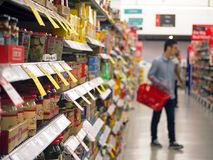 19 de octubre de 2017, estantes por completo de los diversos productos alimenticios con la opinión borrosa un cliente masculino q foto de archivo