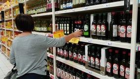 27 de octubre de 2017 Portugal Faro, jumbo La muchacha elige el aceite de oliva para comprar en el supermercado almacen de video