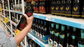 27 de octubre de 2017 Portugal Faro, jumbo La muchacha elige el aceite de oliva para comprar en el supermercado almacen de metraje de vídeo