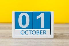 1 de octubre Primer día, el 1 de octubre calendario de madera azul en fondo abstracto amarillo Día del otoño Imagen de archivo libre de regalías