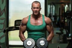 De Oefening van de Bodybuildingsschouder met Domoren Stock Foto