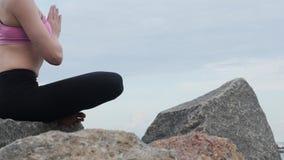 De oefening van de de yogageschiktheid van meisjespraktijken dichtbij de oceaanstrandzitting op de steen in lotusbloem stelt stock video