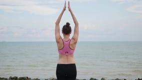 De oefening van de de yogageschiktheid van meisjespraktijken dichtbij de oceaanstrandzitting op de steen in lotusbloem stelt stock videobeelden