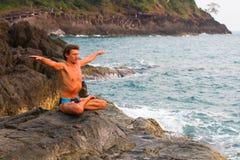 De oefening van de jonge mensenyoga op het verlaten wilde steen overzeese strand nave Stock Afbeeldingen