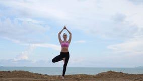 De oefening van de de yogageschiktheid van meisjespraktijken dichtbij het oceaanstrand in boom stelt stock videobeelden
