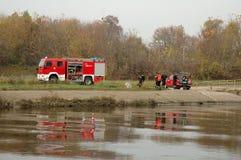 De oefeningen van de brandbrigade op rivierbank Stock Foto's