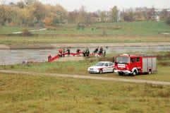 De oefeningen van de brandbrigade op rivierbank Stock Foto