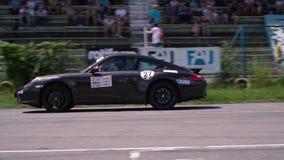 De Oekraïne, Dnipro - Juli 10, 2018: Zwart Porsche reist langs de weg voorbij tribunes met mensen, langzame motie stock footage