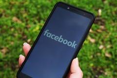 De Oekraïne, Kremenchug - April, 2019: Meisje met smartphone in haar hand en een Facebook-embleem op het scherm Sociaal netwerk stock afbeelding