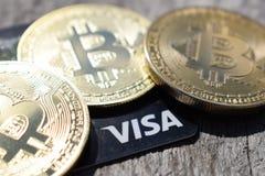 De Oekraïne, Kremenchug - Maart, 2019 Gouden Bitcoins en Visumkaart stock afbeeldingen