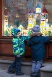 De Oekraïne, Lviv - December 6, 2018 Twee kleine jongens op een Lviv-straat die winkelvenster bekijken die voor Kerstmis wordt ve royalty-vrije stock afbeelding