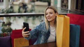 De Oekraïne, Lviv - Februari 2, 2018: Het mooie blondemeisje neemt selfie op haar telefoonzitting in koffie met het winkelen zakk stock video