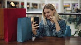 De Oekraïne, Lviv - Februari 2, 2018: Het mooie blondemeisje neemt selfie op haar telefoonzitting in koffie met het winkelen zakk stock footage