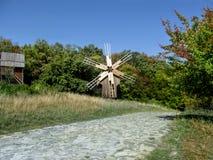 De Oekraïne, Pyrohiv Kiev - 17 September, 2017: Een houten antieke windmolen bevindt zich dichtbij een bos en een bedekte weg in  Stock Fotografie