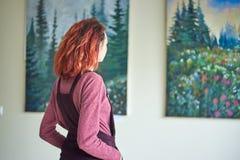 De Oekraïne, Shostka, Art Center, Mira straat - 22 Maart, 2019: Mooi meisje bij een tentoonstelling van schilderijen stock afbeelding