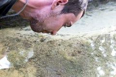 De OEKRAÏNE, Voronizh - September 2, 2018: De man boog over de de lentesleutel van schoon water, welke klappen onder het zand royalty-vrije stock fotografie