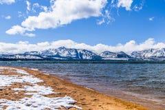 De oever en de sneeuw van Tahoe van het zuidenmeer behandelden zandig strand, op een zonnige dag; de sneeuw behandelde Siërra ber stock afbeeldingen