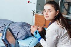 De oftalmoloog voert een handeling uit om het zicht van een jong meisje te diagnostiseren royalty-vrije stock afbeeldingen