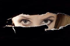 De ogen die van vrouwen door een gat spioneren Stock Foto