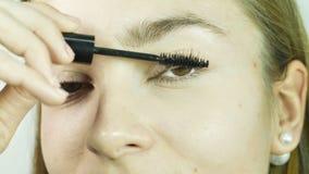 De ogen van het close-upmeisje passen karkas op wimpers, samenstelling in een professionele schoonheidssalon toe stock video