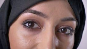 De ogen van jong ernstig moslimmeisje in hijab let op bij camera, grijze achtergrond