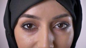 De ogen van jong ernstig moslimmeisje in hijab let op bij camera, het knipperen, grijze achtergrond