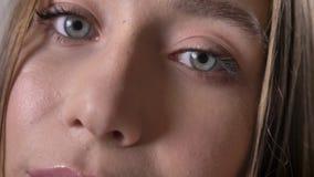 De ogen van jong geheimzinnigheid meisje let op bij camera, het glimlachen, grijze achtergrond stock video