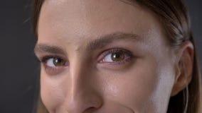 De ogen van jong schuw meisje let op bij camera, het glimlachen, grijze achtergrond stock footage