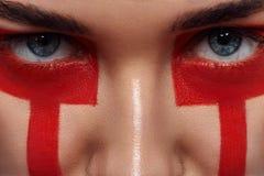 De Ogen van schoonheidsvrouwen ` s en rode Verfstrepen op Gezicht Royalty-vrije Stock Afbeeldingen