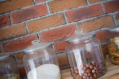 De okkernoten, de deegwaren, de korrels en het zout in glaskruiken in de moderne keuken van het zolderontwerp voor bricked muur,  Royalty-vrije Stock Foto