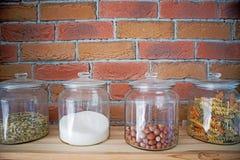 De okkernoten, de deegwaren, de korrels en het zout in glaskruiken in de moderne keuken van het zolderontwerp voor bricked muur,  Stock Fotografie