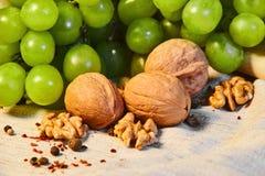 de okkernoten en de groene druiven liggen op linnendoek met kruiden stock afbeeldingen