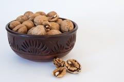 De okkernoten liggen dichtbij in een kom, gehakte noten, op een witte achtergrond royalty-vrije stock foto's