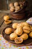 De okkernoten vormen koekjes met condens - dulce DE leche in kleikom op houten rustieke achtergrond Selectieve nadruk Stock Foto