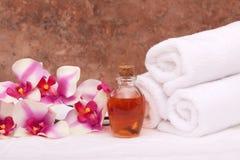 De oliën, de orchidee en de handdoeken van Aromatherapy stock afbeeldingen