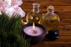 De oliën van de massage, orchideebloem, kiezelstenen op bamboe Stock Afbeeldingen