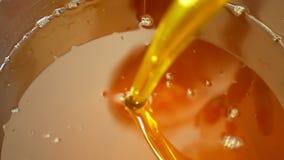 De olie organische kwaliteit van raapzaadcanola bio, actieve bellen, zich mengt en gietend in een staalvat, voor koud voedsel en  stock videobeelden