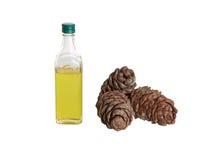 De olie van de ceder in een fles en kegels Stock Afbeeldingen