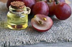 De olie van het druivenzaad in een glaskruik en verse druiven op de achtergrond van de jutedoek Fles de organische olie van het d Royalty-vrije Stock Foto