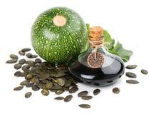 De olie van het pompoenzaad met zaden en installatie royalty-vrije stock afbeeldingen