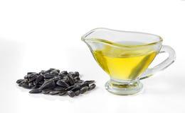 De olie van het zonnebloemzaad en een handvol zonnebloemzaden stock afbeelding