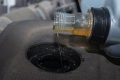 De olie van de nieuwe vullingsmotor in de auto stock foto