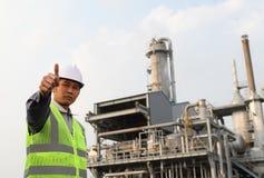 De olieraffinaderij van de ingenieur met duimen op gebaar Stock Fotografie